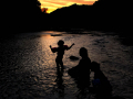 Lilybelle Erdrich sings a song for her mother Nellie Doneva and sister Willow as the sun sets behind her on the Paluxy River at Dinosaur Valley State Park June 21, 2020.
