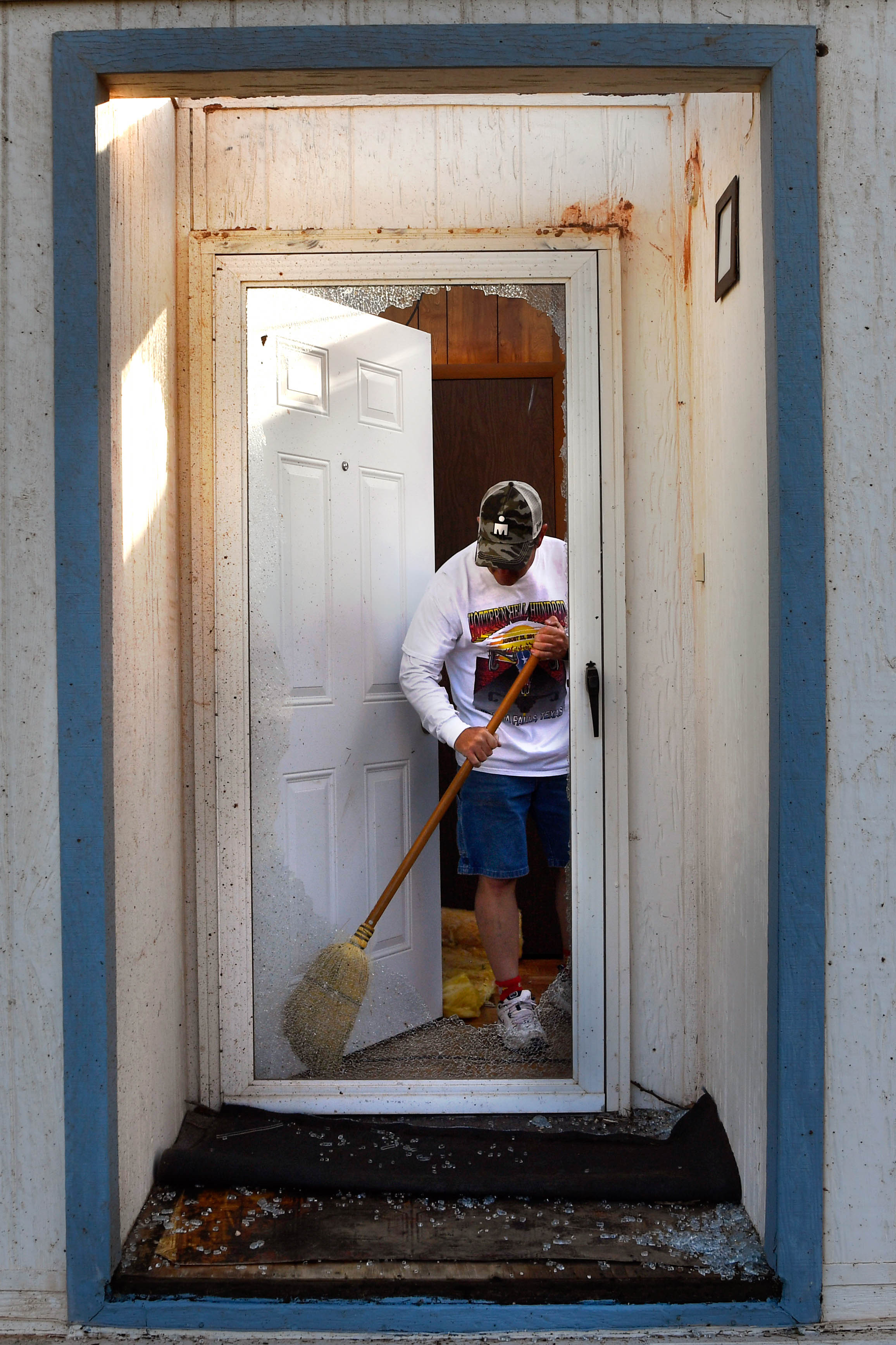"""William """"J.R."""" Brock sweeps glass from his shattered front doorway Thursday morning March 19, 2020. The Tye resident was awakened about 1:30 a.m. by the sound of the Dyess Air Force Base sirens as a tornado swept over his neighborhood. Brock was able to get his wife Kristi, her mother, and their two dogs into a storm shelter before the roof was taken off their home."""