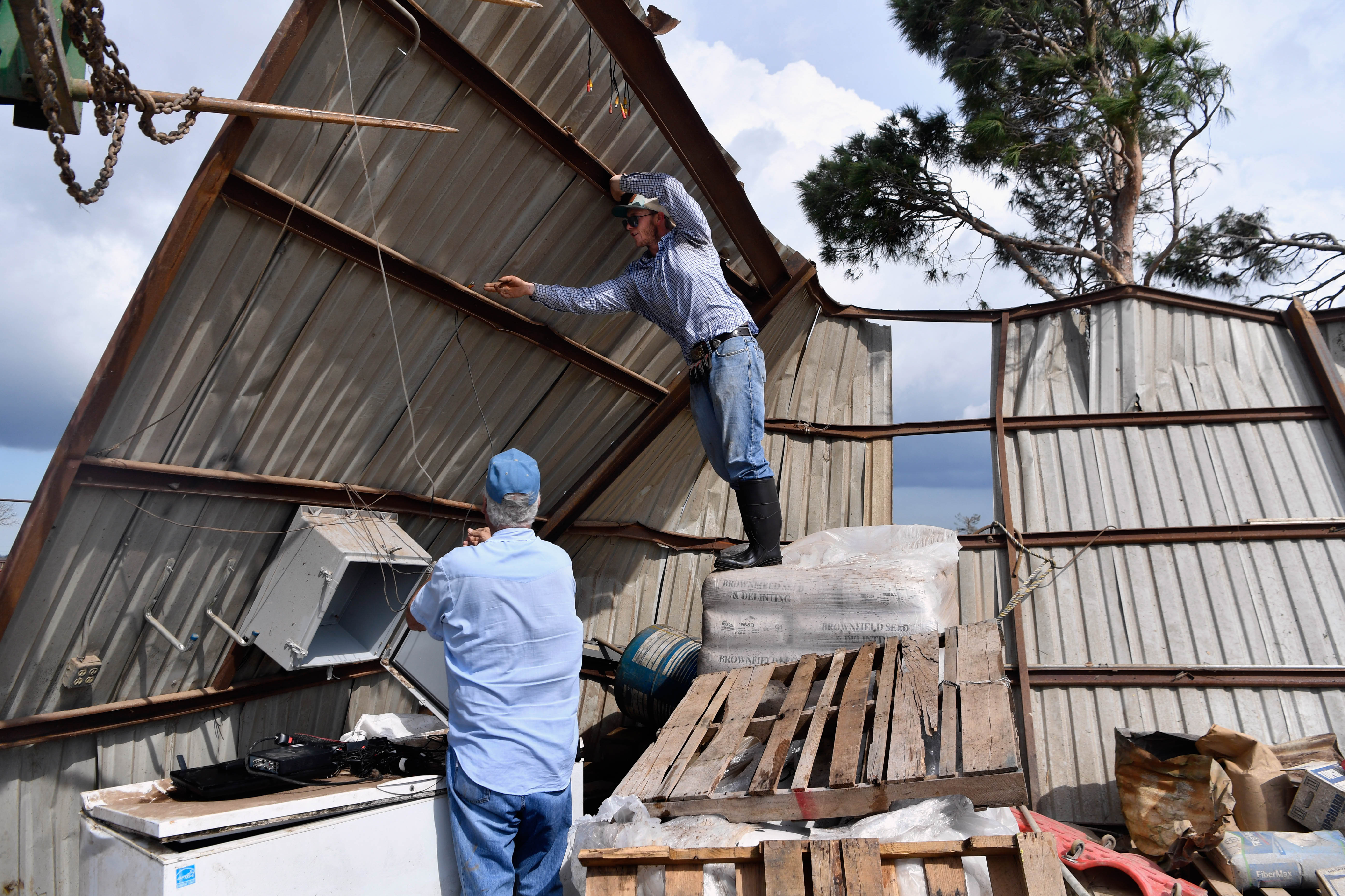 Marshal Mepps stands atop a pallet of supplies inside the remains of Randall Franke's workshop Thursday March 19, 2020. Danny Lewis, Franke's brother-in-law, watches. At least three tornadoes were confirmed to have swept through the Abilene area earlier in the day around 1:30 a.m.