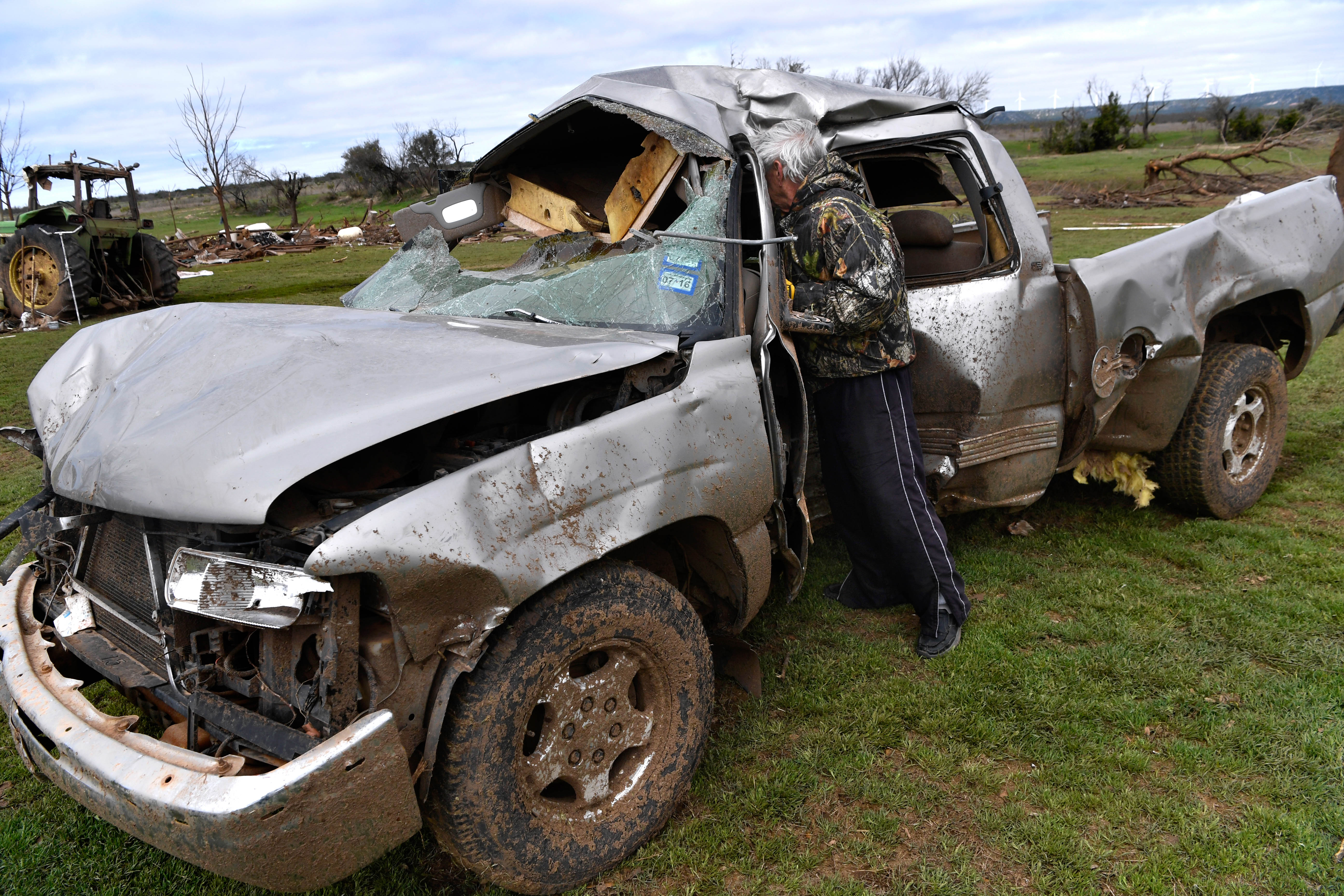 Gary Doan steps into the tree-shaped dent in one of his pickups to retrieve ammunition from the ruined vehicle's center console Friday March 20, 2020. The pickup had been damaged Thursday when a tornado picked it up in the early morning hours on their ranch in the Mulberry Canyon area south of Merkel.