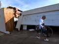 """William """"J.R."""" Brock carries a pair of bicycle tires out of his toppled garage Thursday March 19, 2020. A tornado damaged his Tye home early that morning, but not before he and his family made it to their storm shelter."""