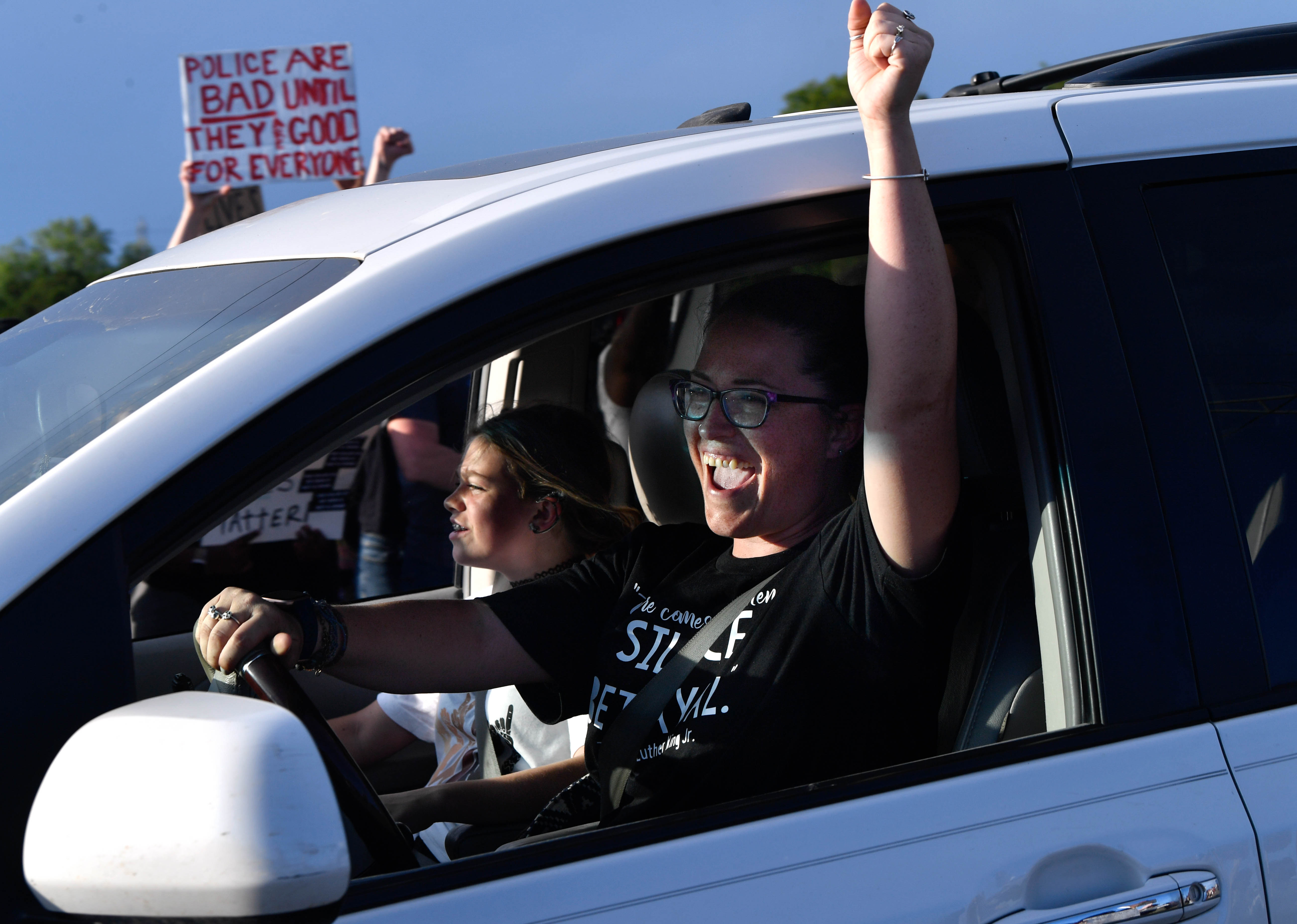 A woman raises her hand in solidarity as she passes a crowd Thursday demonstrating to remember national victims of police brutality June 4, 2020. E. Highway 80 was eventually closed as people gathered to march from the Martin Luther King Jr. sign into downtown Abilene and back.