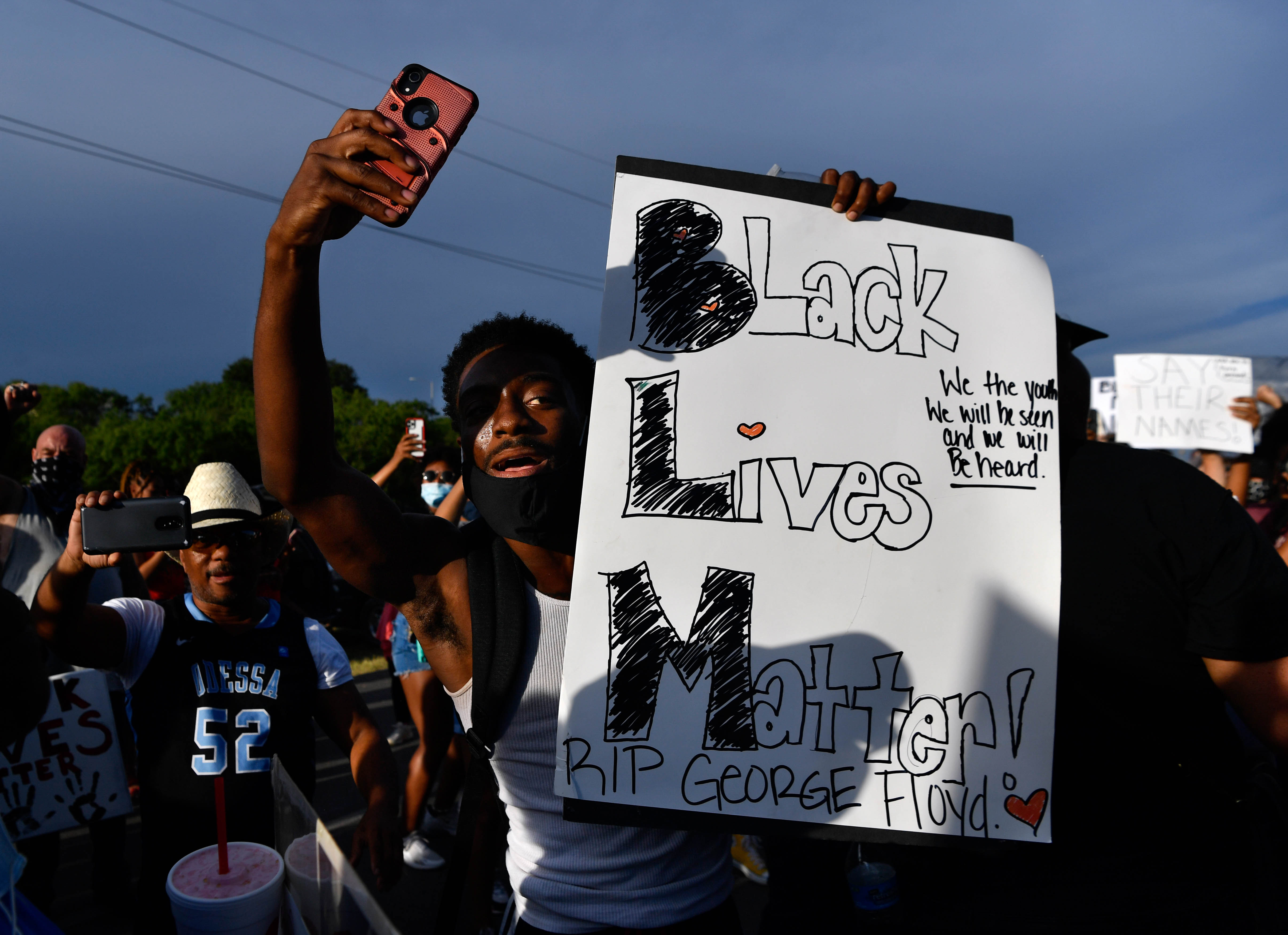 A demonstrator records video while holding a sign as a crowd fills E. Highway 80 at Cockerell Dr. Thursday June 4, 2020. The group was rallying against racism and national acts of police brutality.