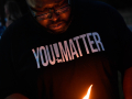 Matthias Royals lights a candle in memory of George Floyd at the conclusion of Thursday's march June 4, 2020. A group stayed behind to join in a circle of silence for eight minutes and forty-six seconds, the time George Floyd was held down by Minneapolis police until he died.