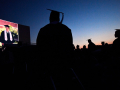 Eula High School graduates are silhouetted in the twilight as they watch the slide show of their classmates during commencement May 22, 2020. The district rented Abilene's Town & Country Drive-In Theatre as an open-air option for graduation during the coronavirus pandemic.