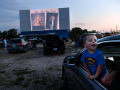 Zachai Castillo, 2, stands in the lap of Michael Tatum as he looks around at the other cars watching the slide show of graduating seniors at the Town & Country Drive-In Theatre May 22, 2020. Thirty Eula High School students graduated there, the district having rented the theater to comply with pandemic restrictions.